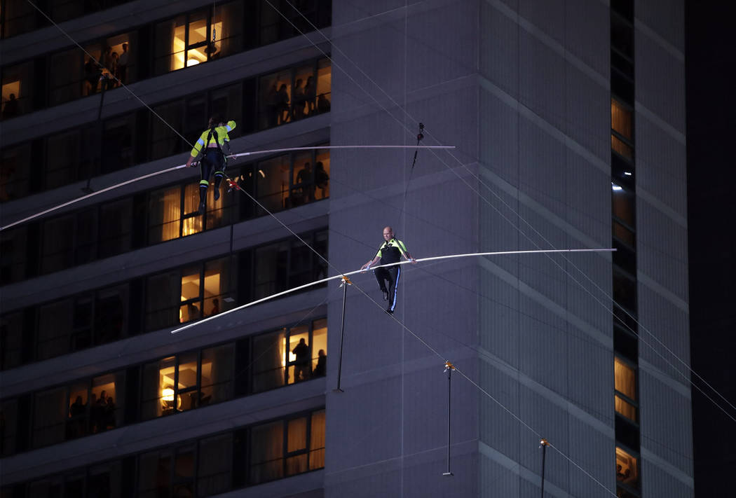 Aerialists Nik Wallenda, right, and his sister Lijana walk on a high wire above Times Square, S ...