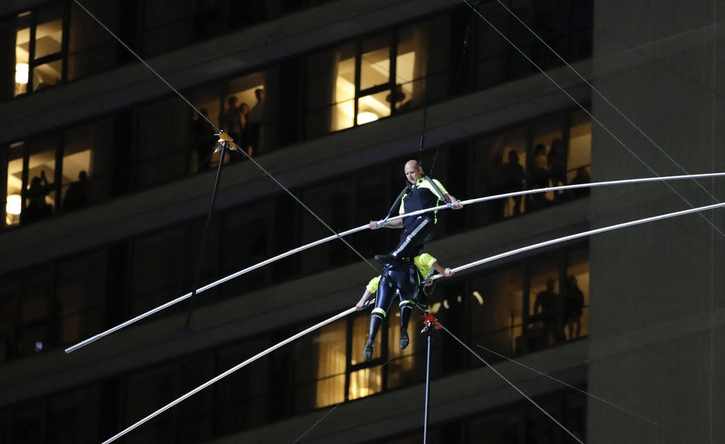 Aerialists Nik Wallenda, top, steps over his sister Lijana as they walk on a high wire above Ti ...