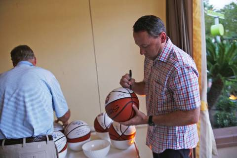 Jack Murphy, coach for Northern Arizona University, signs a basketball at the Coach vs. Cancer ...