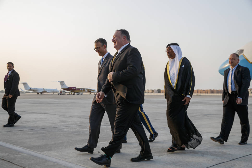 Secretary of State Mike Pompeo, center, walks with U.S. Charge d'Affaires Steve Bondy, left, an ...