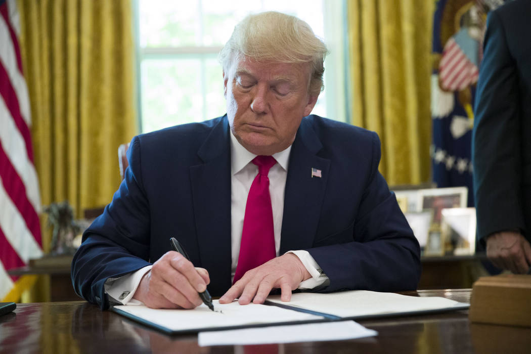 President Donald Trump signs an executive order to increase sanctions on Iran, in the Oval Offi ...