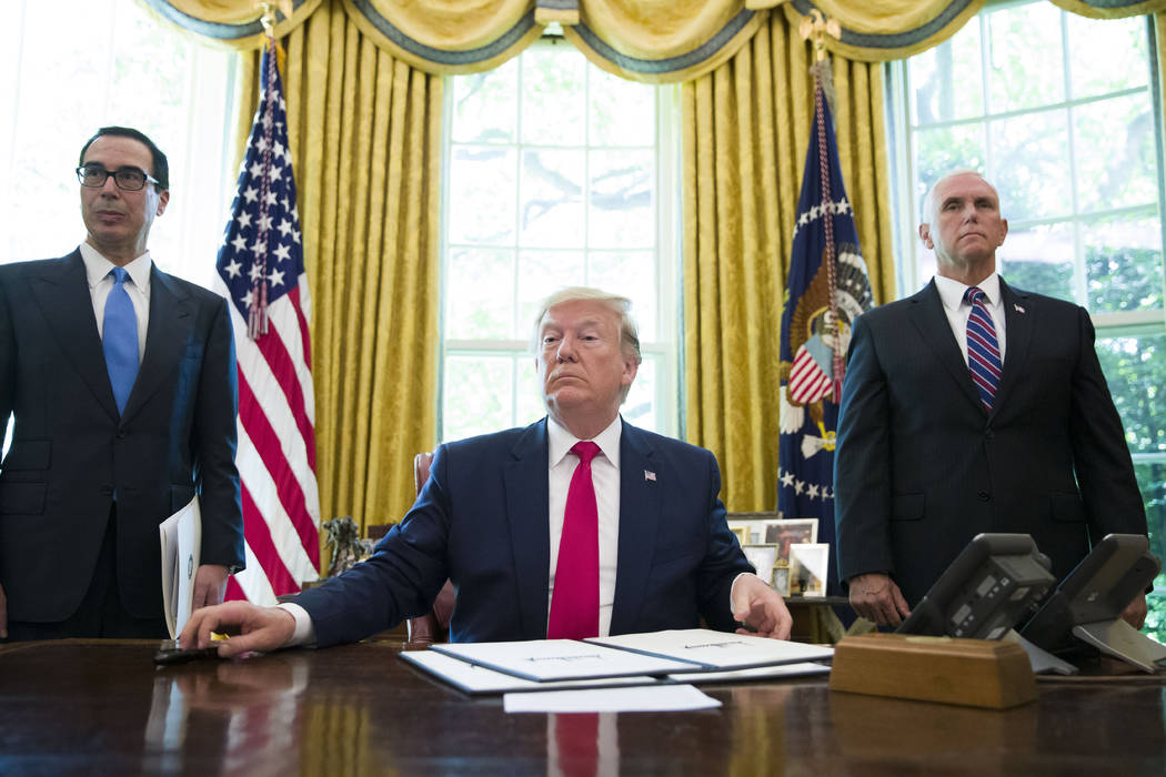 President Donald Trump listens to a reporter's question after signing an executive order to inc ...