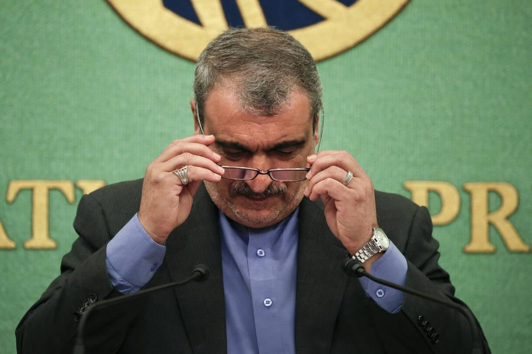 Iranian Ambassador to Japan Morteza Rahmani Movahed puts on his reading glasses before speaking ...