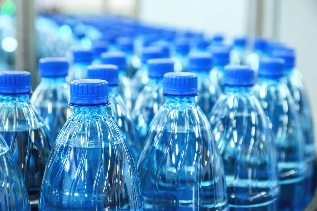 Closeup on mineral water green bottles in raw and lines