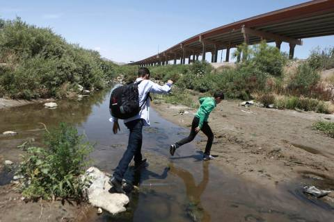 In a June 7, 2019, file photo, people cross the Rio Grande into the United States to turn thems ...