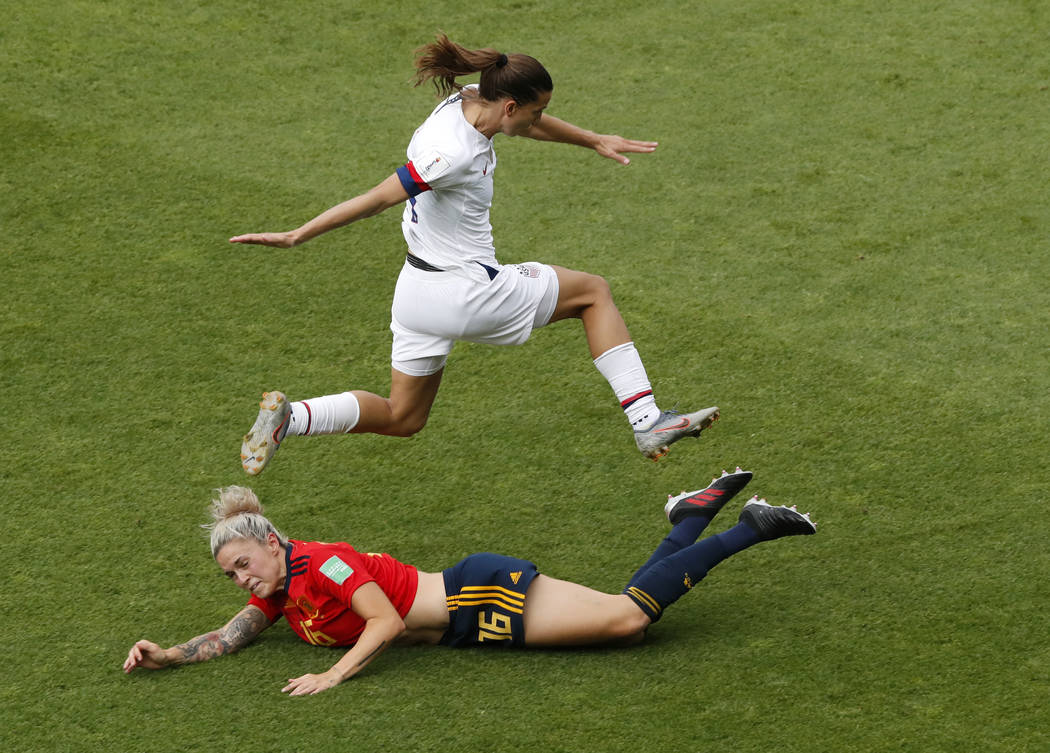 United States' Tobin Heath, top, jumps over Spain's Maria Leon during the Women's World Cup rou ...
