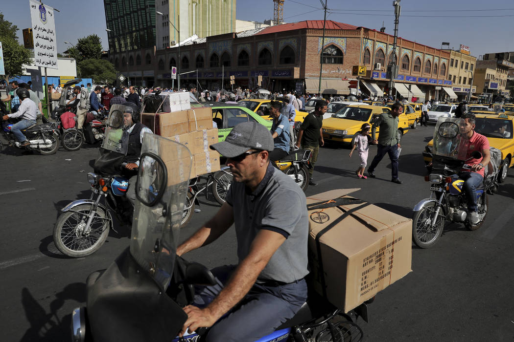 Motorbike taxi divers carry goods at the old main bazaar in Tehran, Iran, Sunday, June 23, 2019 ...