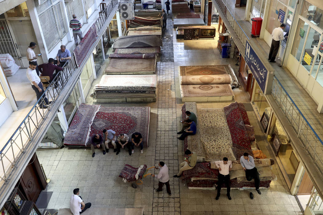 Iranian merchants conduct their business at a carpet market of the old main bazaar in Tehran, I ...