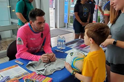 Las Vegas Lights goalie Thomas K. Olsen signs a soccer ball for unidentified young soccer playe ...
