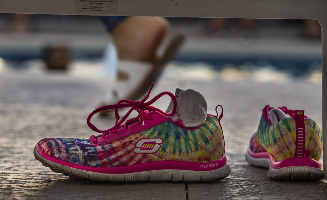 Rainbow sneakers are left under a lounge chair in the pool area during Pride Night at the Las V ...