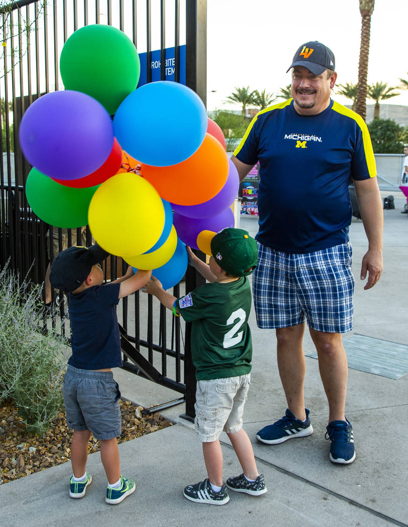 Anthony Allen, 3, and Donald Allen, 4, play with colored balloons as Kevin Lecik looks on about ...