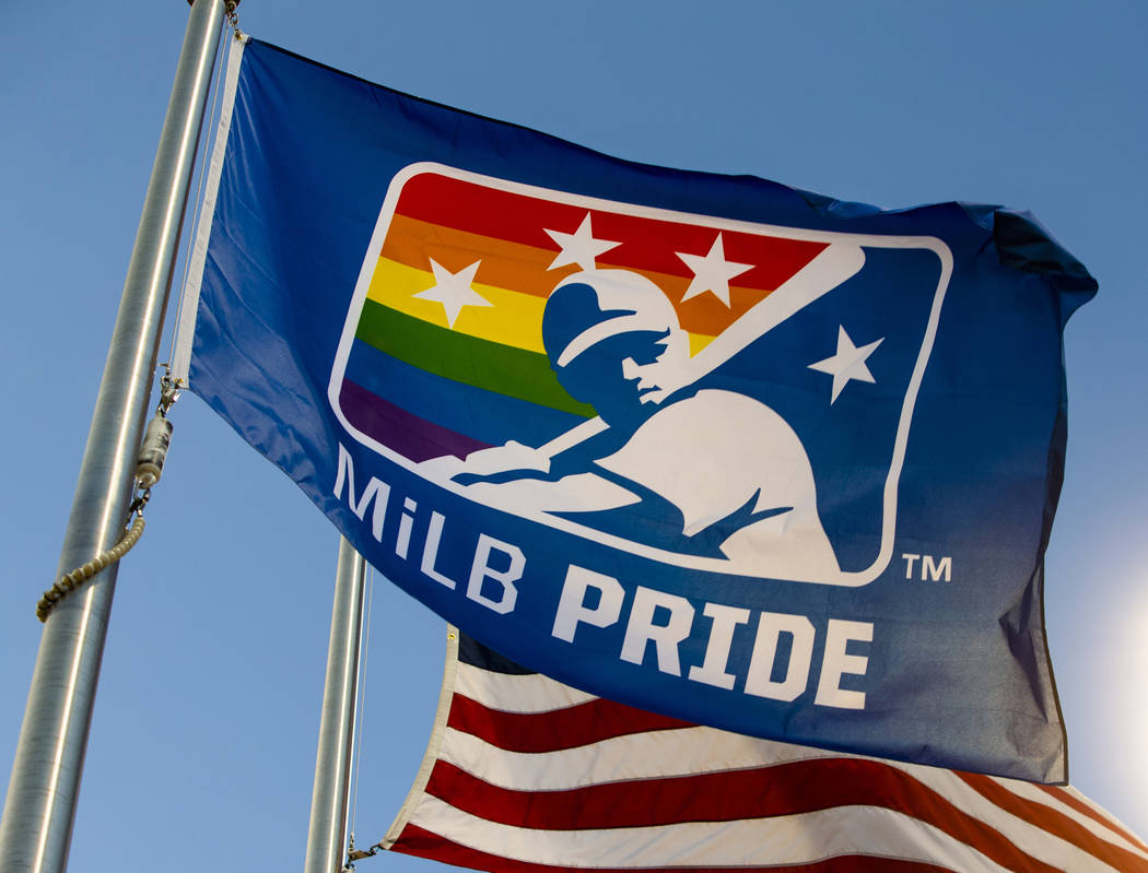 An MiLB Pride flag hangs next to the American flag beyond right field during Pride Night at the ...