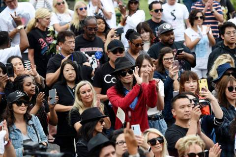 Fans of Michael Jackson including Jackson impersonator Rem Garza, center, stand outside the lat ...