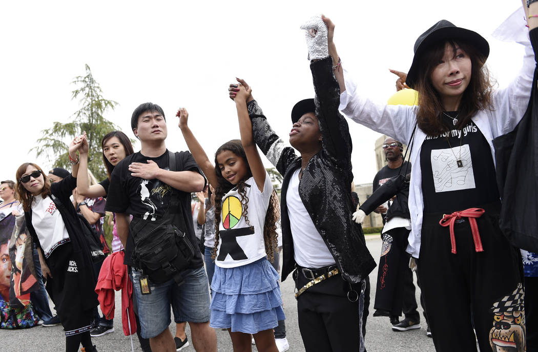 Michael Jackson fans join hands during a group prayer outside the late pop star's final resting ...