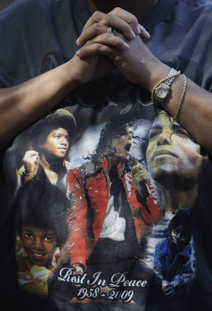 FILE - This June 30, 2009 file photo shows a fan wearing a Michael Jackson T-shirt at a makeshi ...