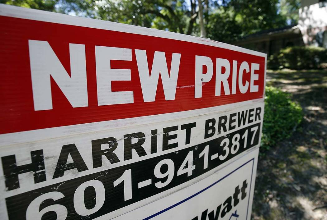 """A June 13, 2019, photo a house on the market has a """"new price"""" sign fixed on the Realtor's sign ..."""
