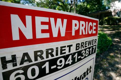 "A June 13, 2019, photo a house on the market has a ""new price"" sign fixed on the Realtor's sign ..."