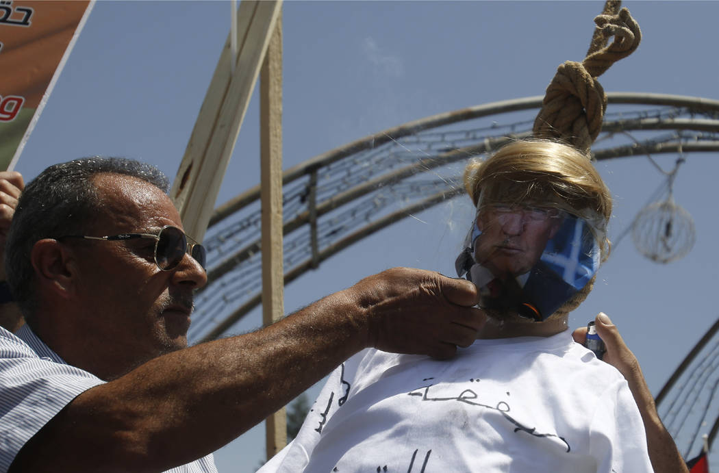 A Palestinian burns an effigy of the US President Donald Trump aduring a protest against the Am ...