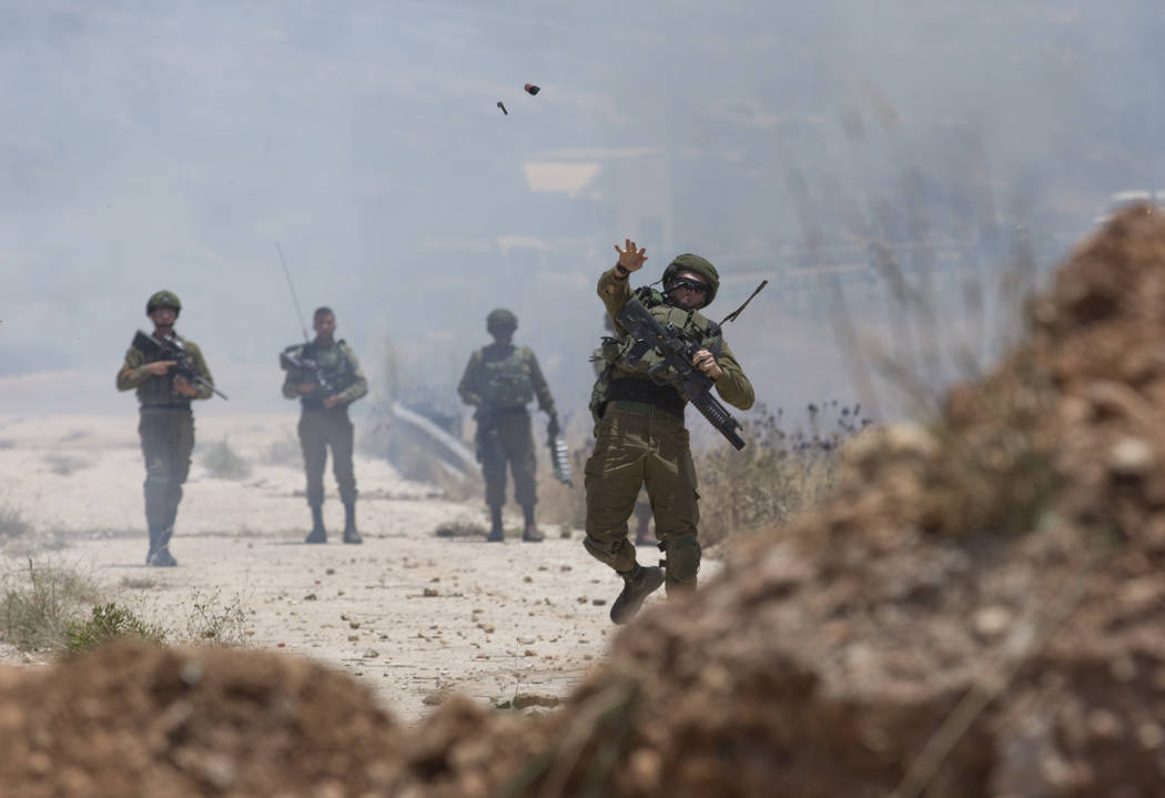 Israeli border police use teargas to disperse Palestinian protesters during a rally against the ...