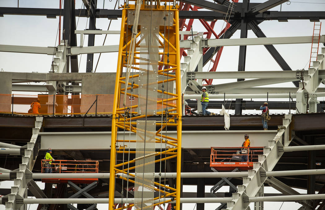 Steelworkers maneuver about the interior of the Raiders Stadium as construction continues on Tu ...
