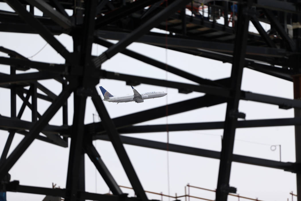 A plane takes flight on the background of the Raiders stadium construction site in Las Vegas, T ...