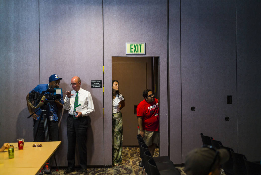 UNLV students Lynnette Hull, center, and Max Gonzalz, right, watch the Democratic presidential ...