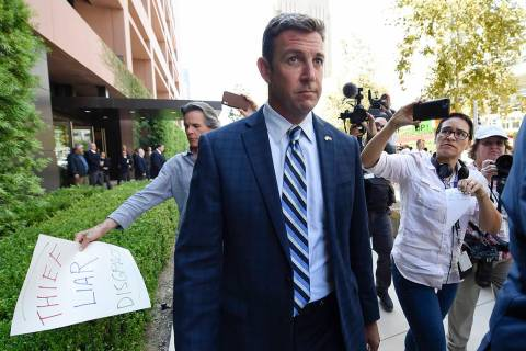 U.S. Rep. Duncan Hunter, center, leaves an arraignment hearing as a protester carries a sign, l ...