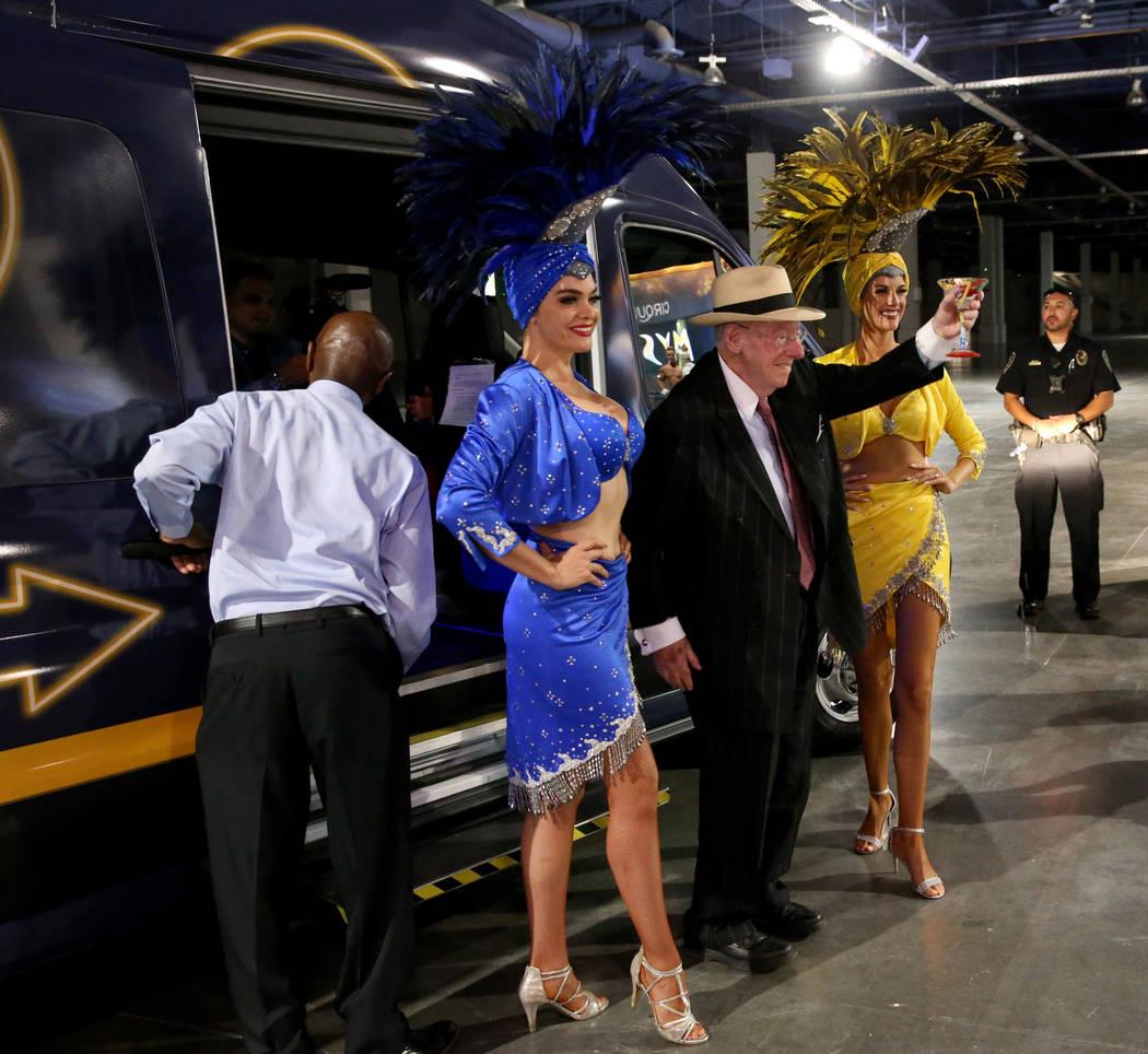 Former Mayor Oscar Goodman exits an 11-passenger shuttle with Showgirls Porsha Revesz, left, an ...