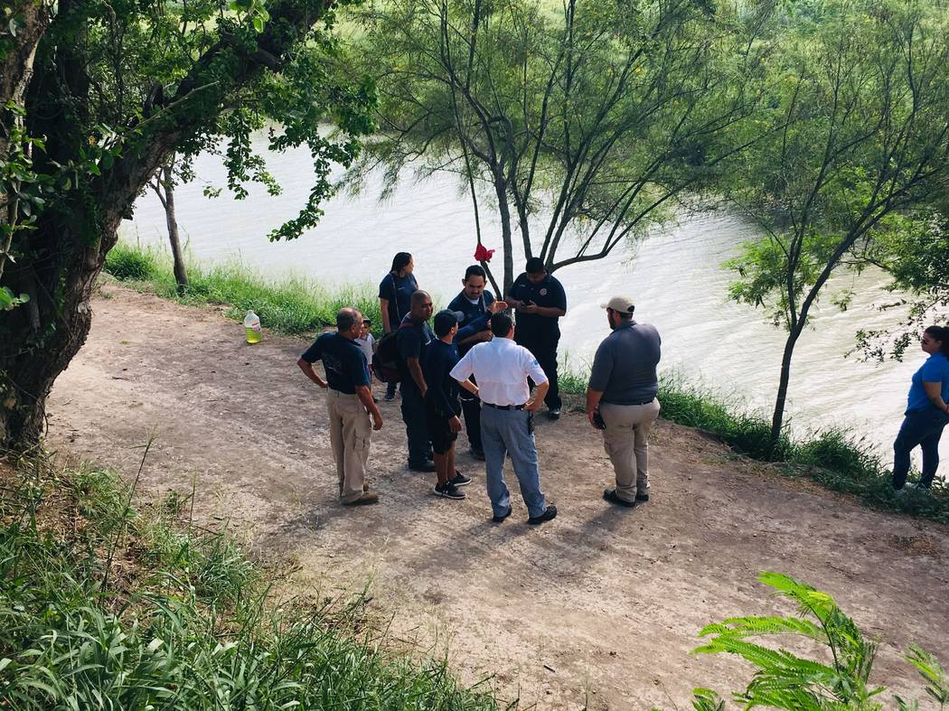 Mexican authorities stand along the Rio Grande bank where the bodies of Salvadoran migrant Osca ...
