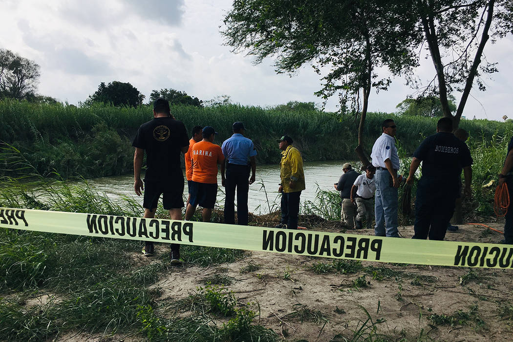 Authorities stand behind yellow warning tape along the Rio Grande bank where the bodies of Salv ...