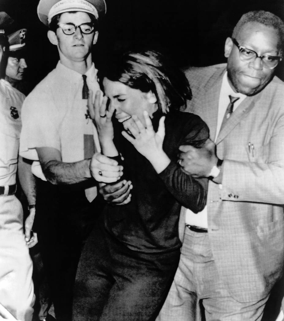 In this Aug. 21,1964 file photo an overwrought Beatles fan is escorted from the hall during the ...