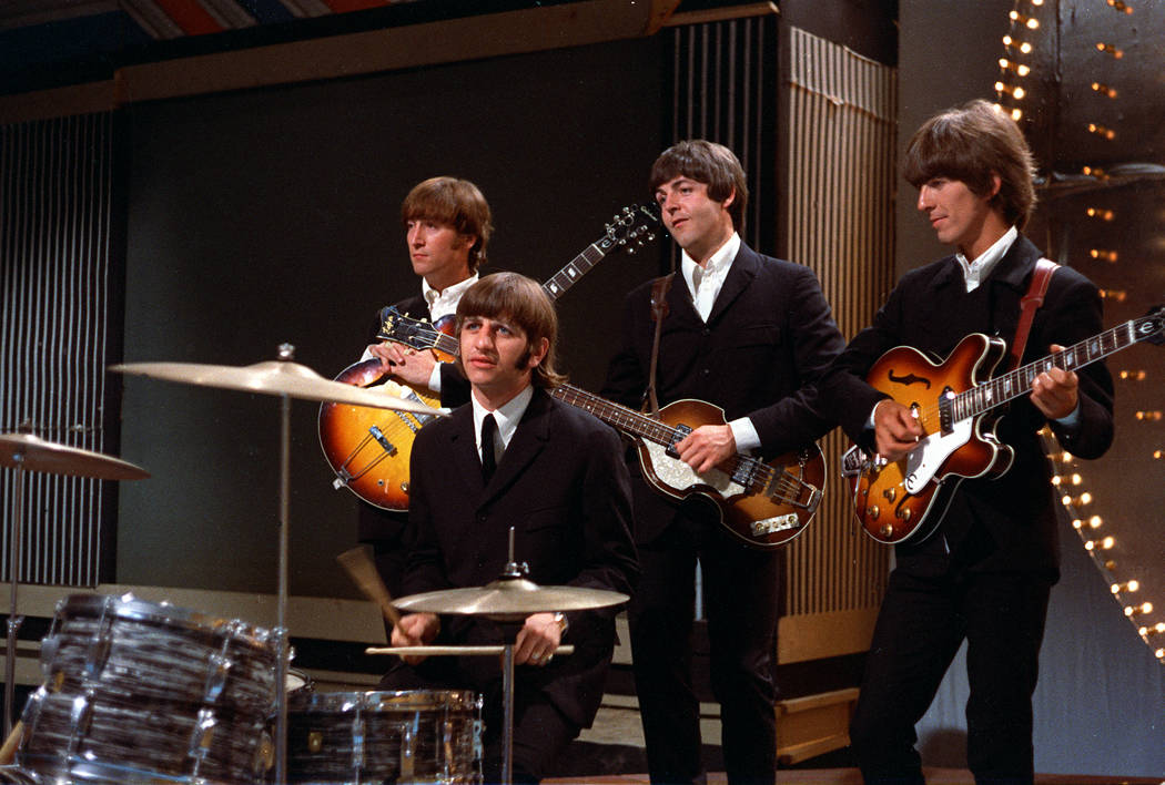 The Beatles pose together before their performance in a TV studio in London, England, in 1966. ...