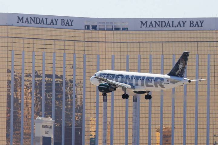 A Frontier Airlines flight passes in front of the Mandalay Bay hotel-casino on approach to McCa ...