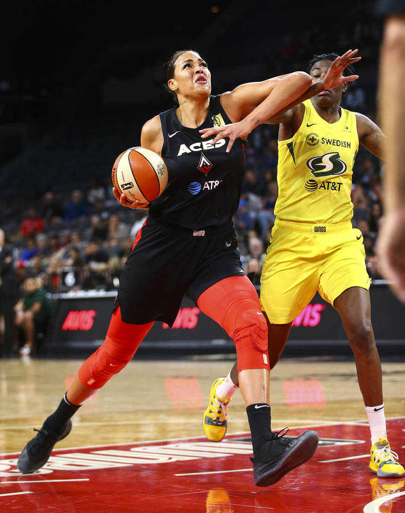 Las Vegas Aces center Liz Cambage, left, drives to the basket against Seattle Storm forward Nat ...