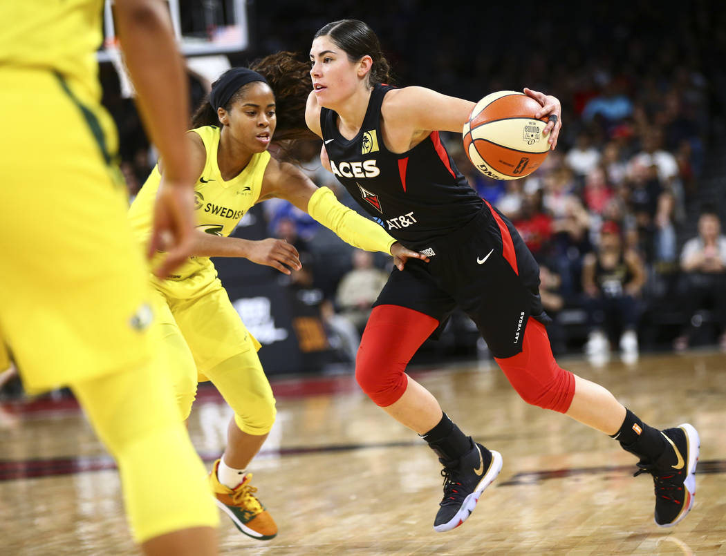 Las Vegas Aces guard Kelsey Plum, right, drives against Seattle Storm guard Jordin Canada durin ...