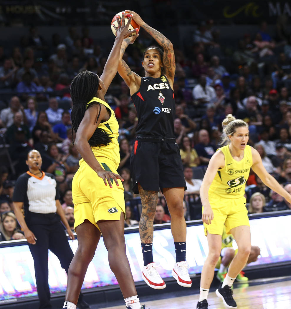 Las Vegas Aces forward Tamera Young shoots over Seattle Storm forward Crystal Langhorne during ...
