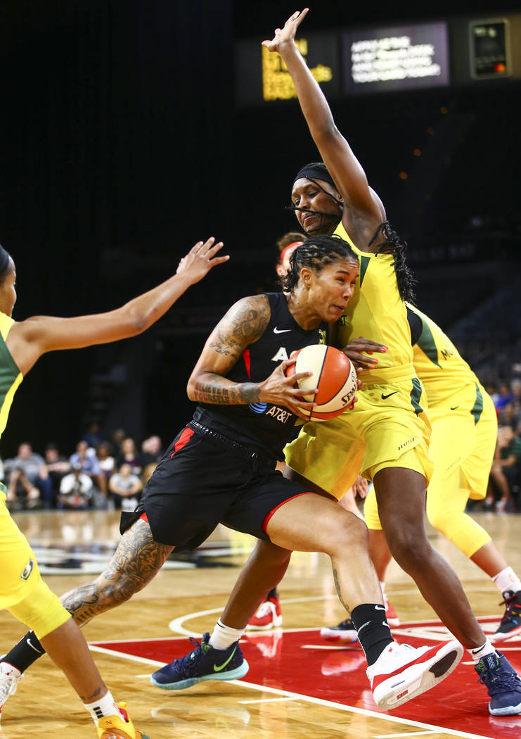 Las Vegas Aces forward Tamera Young, left, drives to the basket against Seattle Storm forward C ...