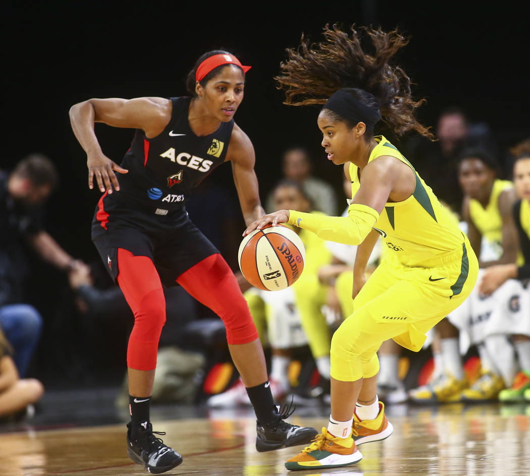 Seattle Storm guard Jordin Canada, right drives the ball under pressure from Las Vegas Aces gua ...