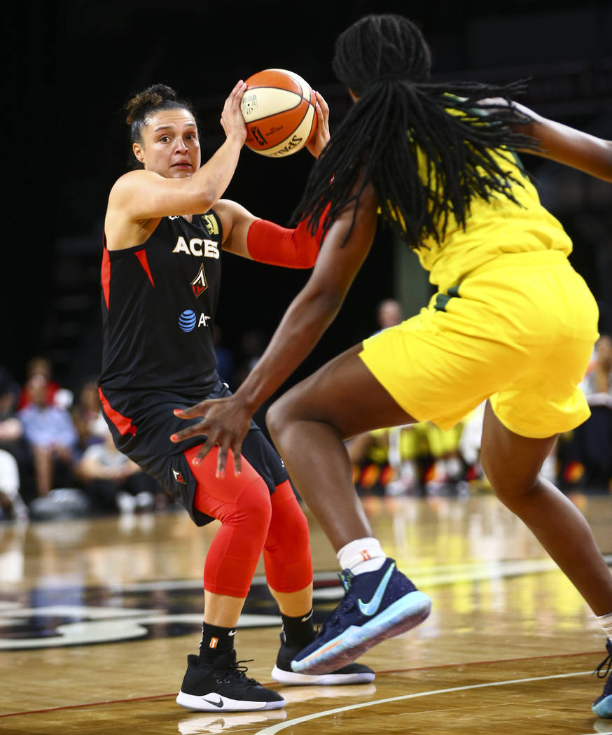 Las Vegas Aces guard Kayla McBride, left, looks to move the ball around Seattle Storm forward C ...