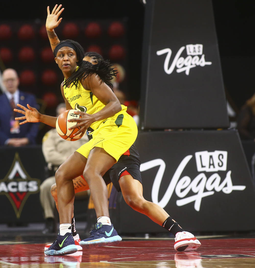 Seattle Storm forward Crystal Langhorne moves the ball around a Las Vegas Aces defender during ...