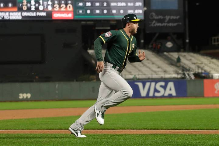 Oakland Athletics' Eric Campbell scores against the San Francisco Giants during the seventh inn ...