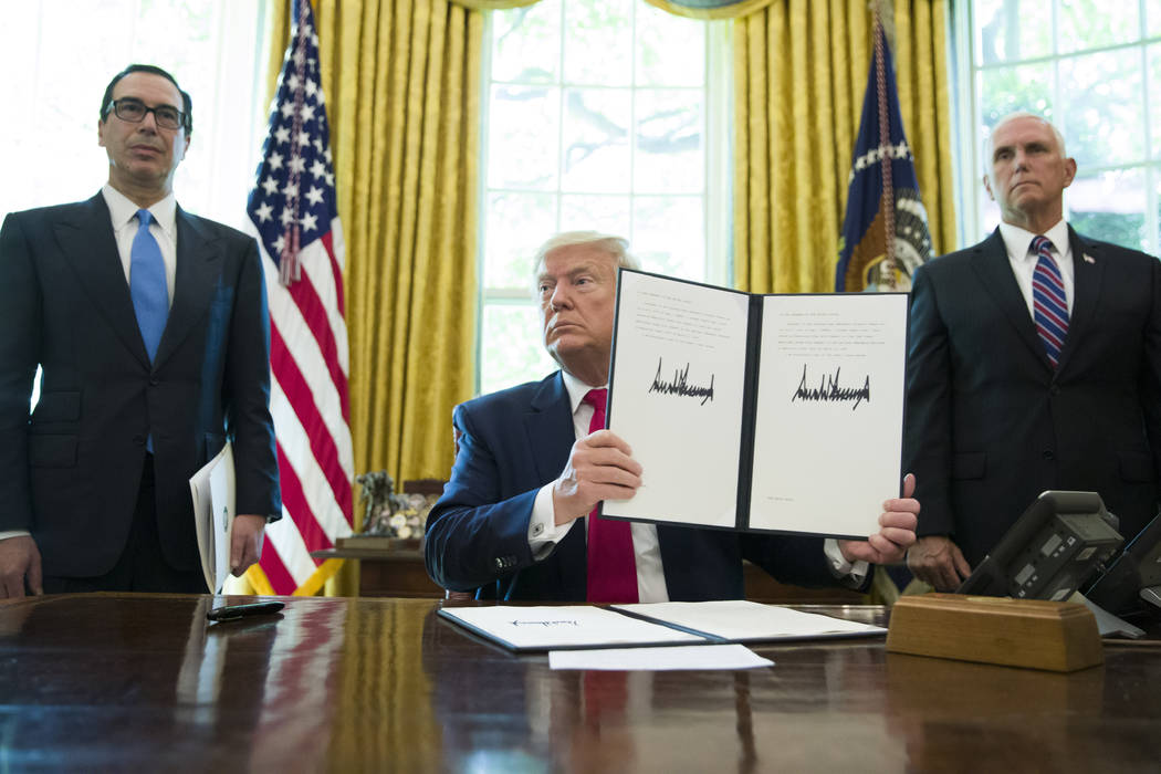 President Donald Trump holds up a signed executive order to increase sanctions on Iran, in the ...