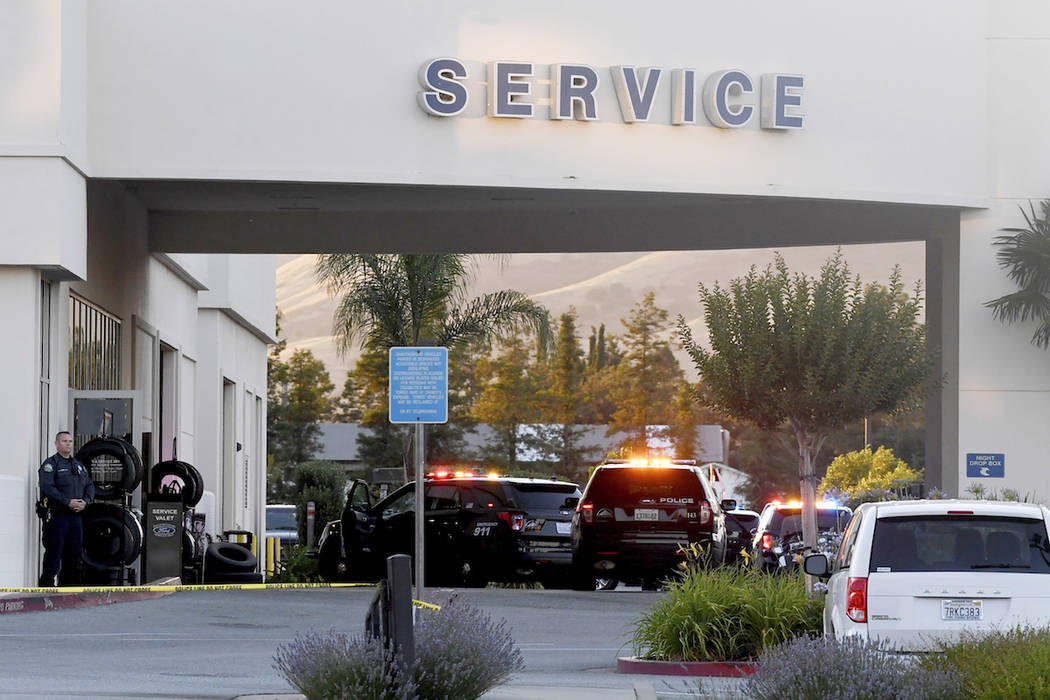 Police investigate at the scene of a shooting at the Morgan Hill Ford Store in Morgan Hill, Cal ...