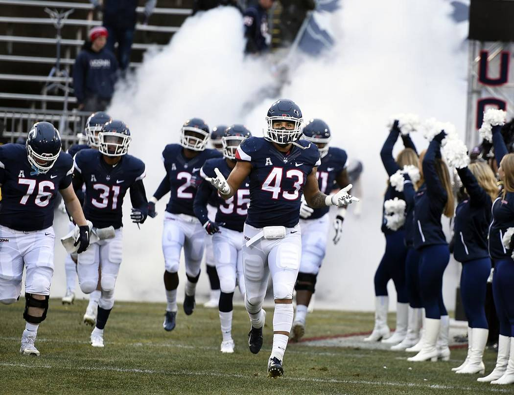 In this Nov. 24, 2018, file photo, Connecticut linebacker Darrian Beavers (43) leads his team o ...