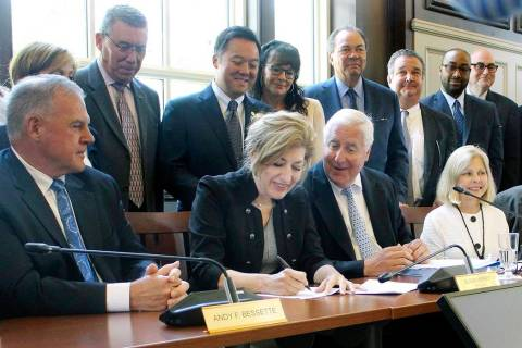 University of Connecticut President Susan Herbst, seated center, signs a contract on Wednesday, ...