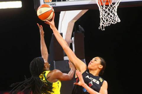 Las Vegas Aces center Liz Cambage, right, blocks a shot from Seattle Storm forward Crystal Lang ...