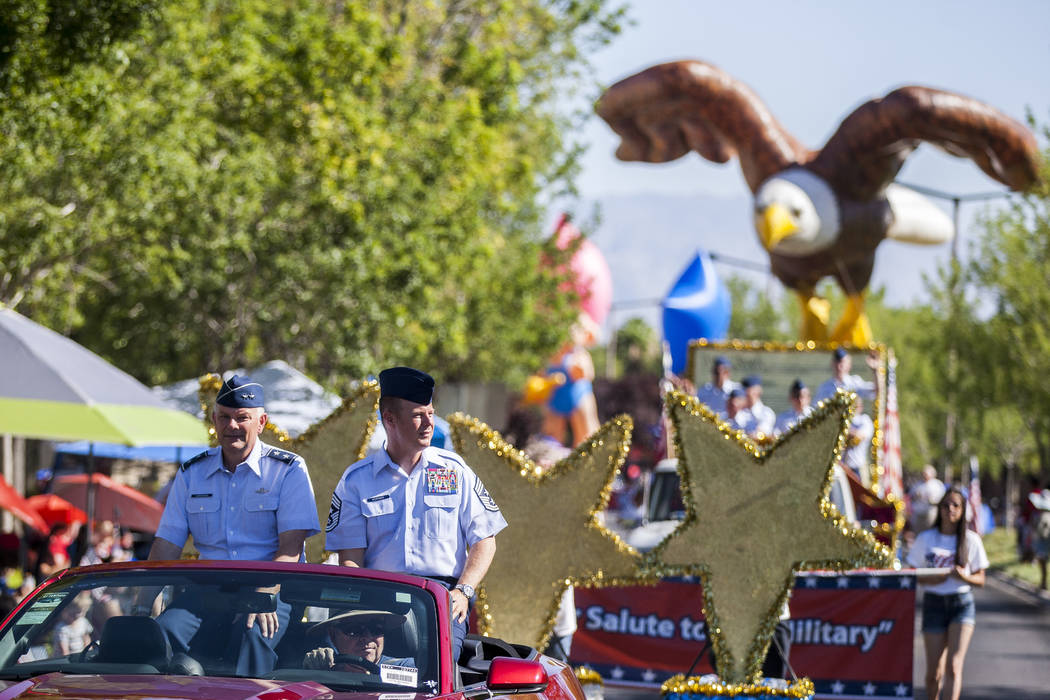 Servicemen drive by with an eagle float in the background during the Summerlin Council Patrioti ...
