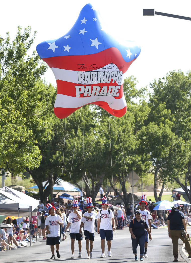 Participants walk with a patriotic star balloon to start the Summerlin Council Patriotic Parade ...