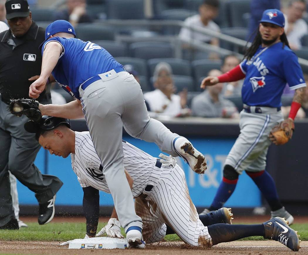 Toronto Blue Jays starting pitcher Clayton Richard (2) steps over New York Yankees' Giancarlo S ...