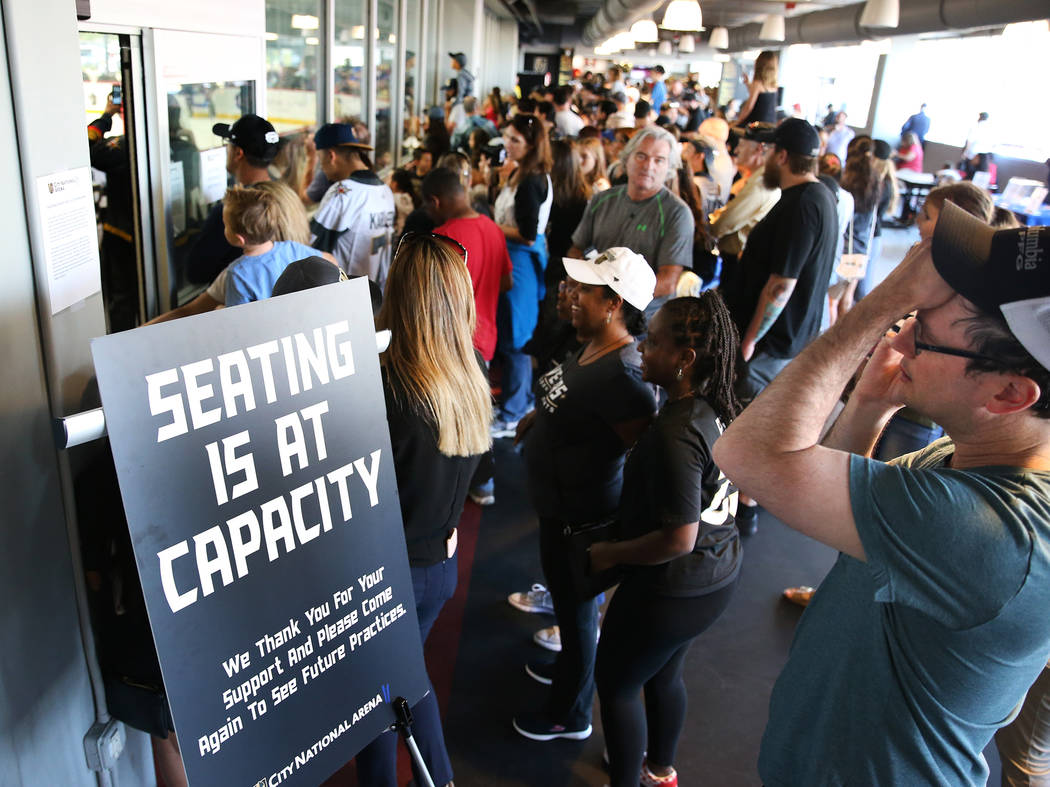 Fans watch the Vegas Golden Knights practice from a hallway after seating was at maximum capaci ...